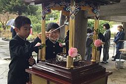 花御堂で甘茶をかけてお釈迦さまの誕生を祝います